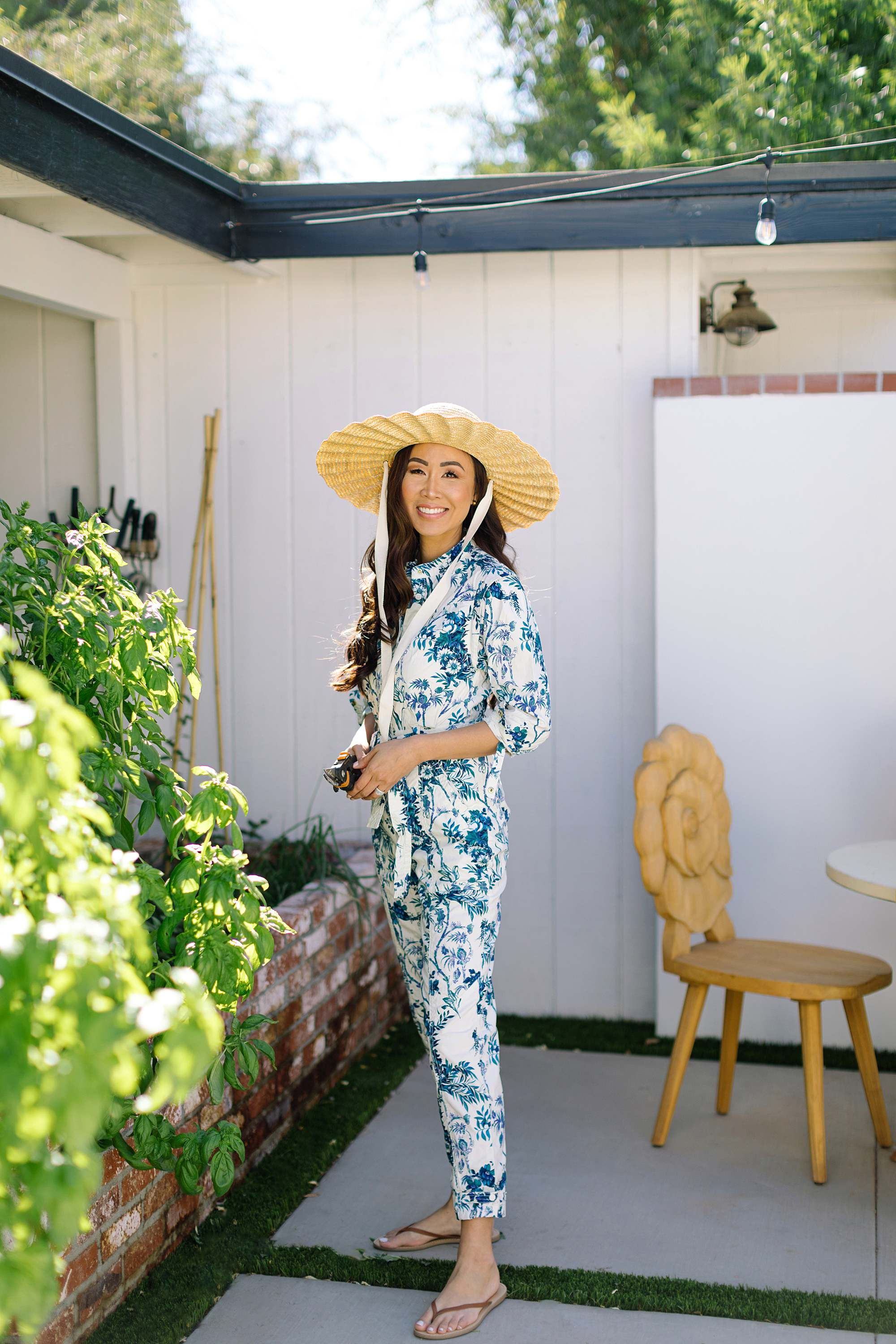 blue and white print jumpsuit wearing straw hat gardening in Phoenix Arizona lifestyle blogger talking about home ownership dreams