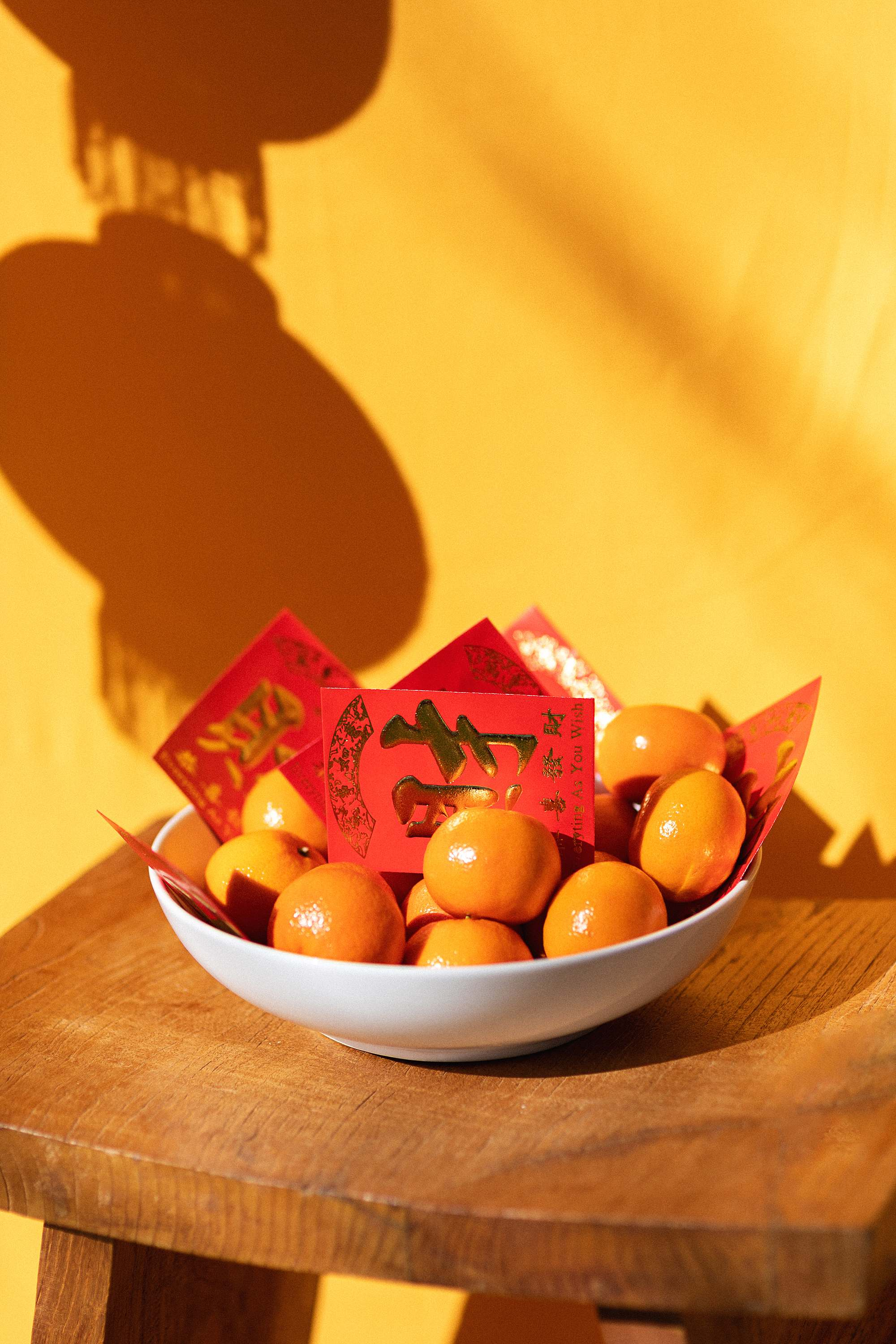 mandarin oranges in a bowl with red envelopes Chinese New Year - Chinese New Year lunar new year outfit and festivities - growing up Asian American blog post - DianaElizabethblog.com