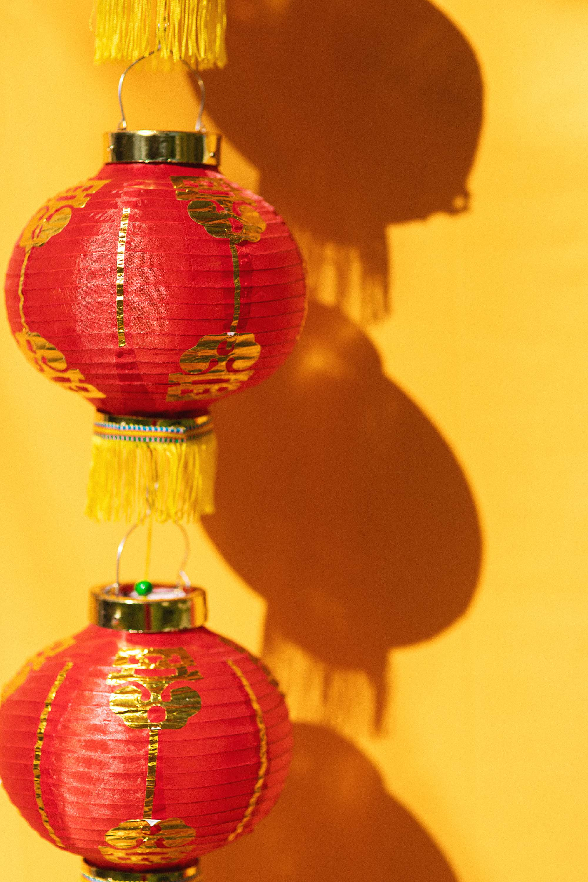 Lunar new year - red lantern on yellow backdrop with shadows Chinese New Year - Chinese New Year lunar new year outfit and festivities - growing up Asian American blog post - DianaElizabethblog.com (c) Diana Elizabeth Photography, LLC