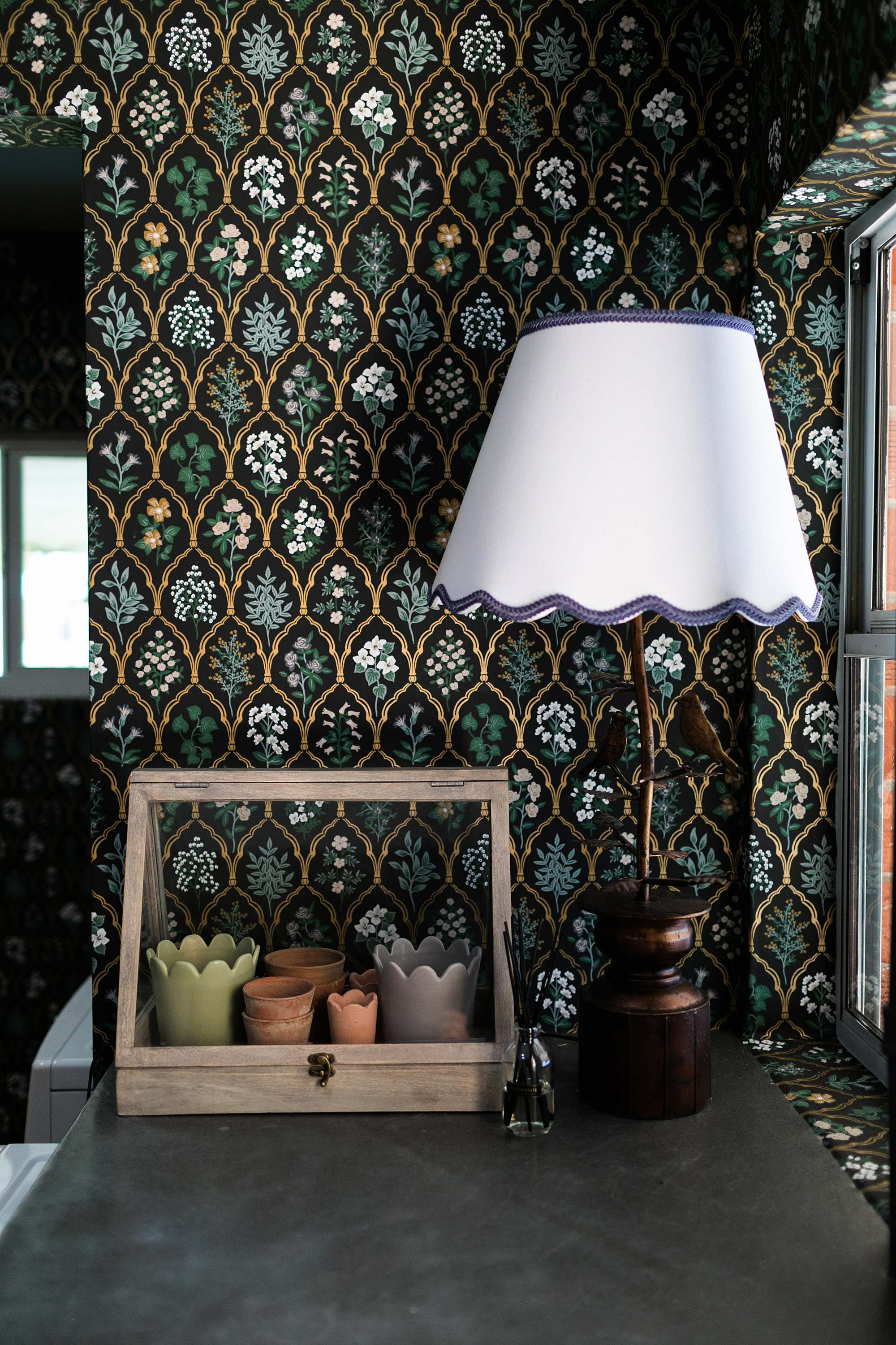 small A frame greenhouse scalloped garden pots scalloped lamp shade on bird lamp / scalloped jute rug rifle paper co. Hawthorne wallpaper black linen floral wallpaper in mudroom laundry room English cottage vibes grandmillennial style - dianaelizabethblog.com