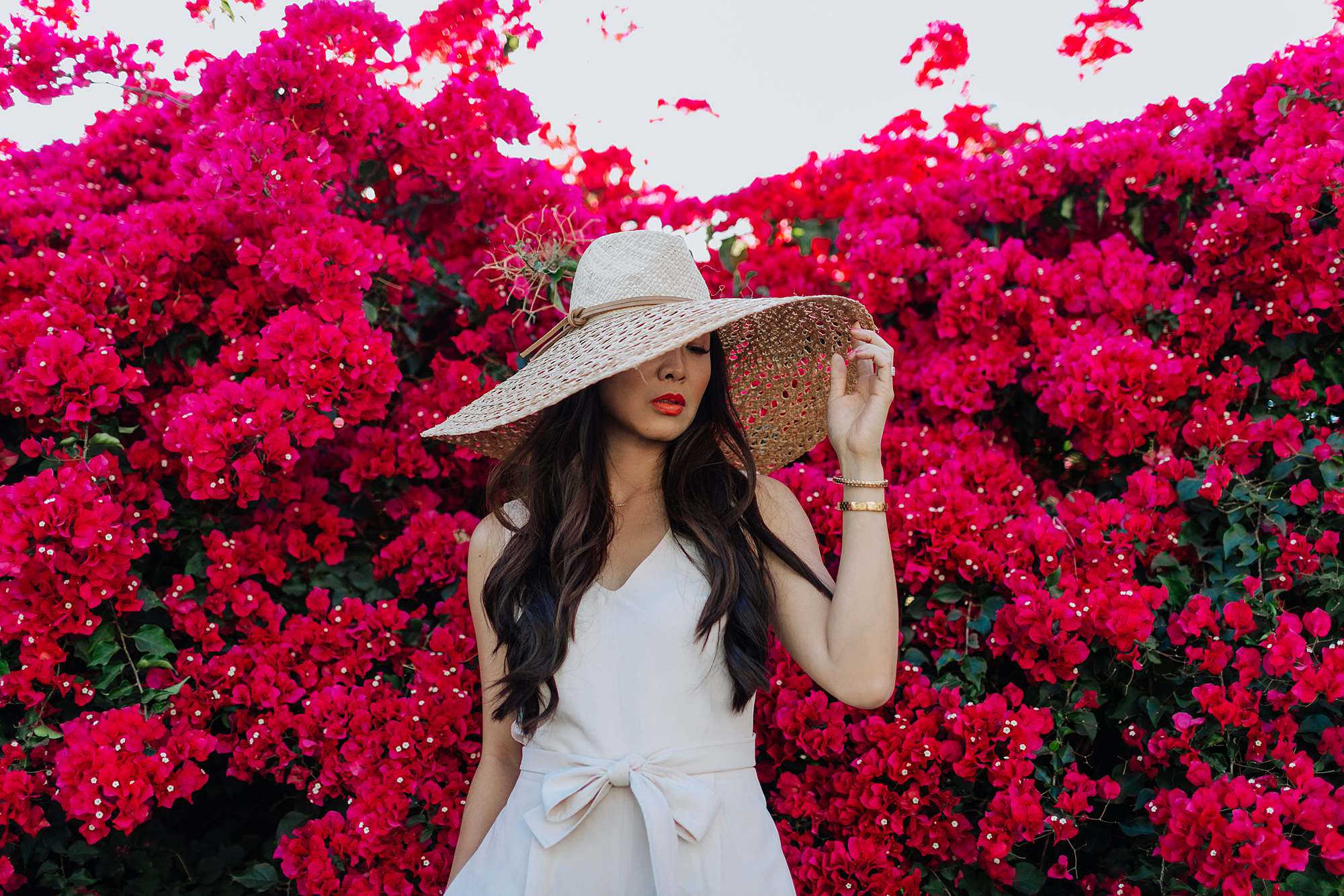 woman in pink jumpsuit infant of Bougainvillea plant wearing large straw hat oversized