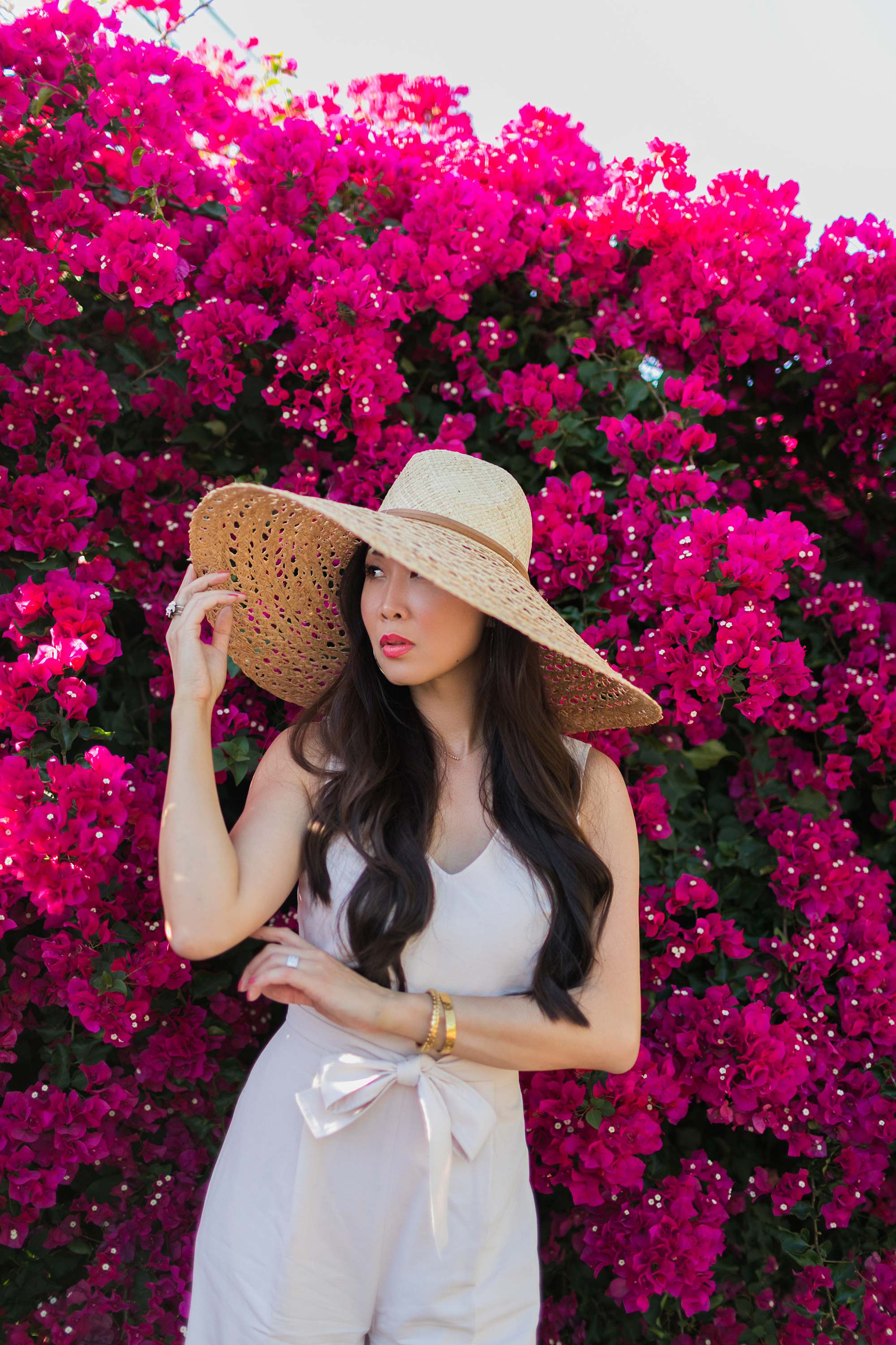 woman in pink jumpsuit infant of Bougainvillea plant