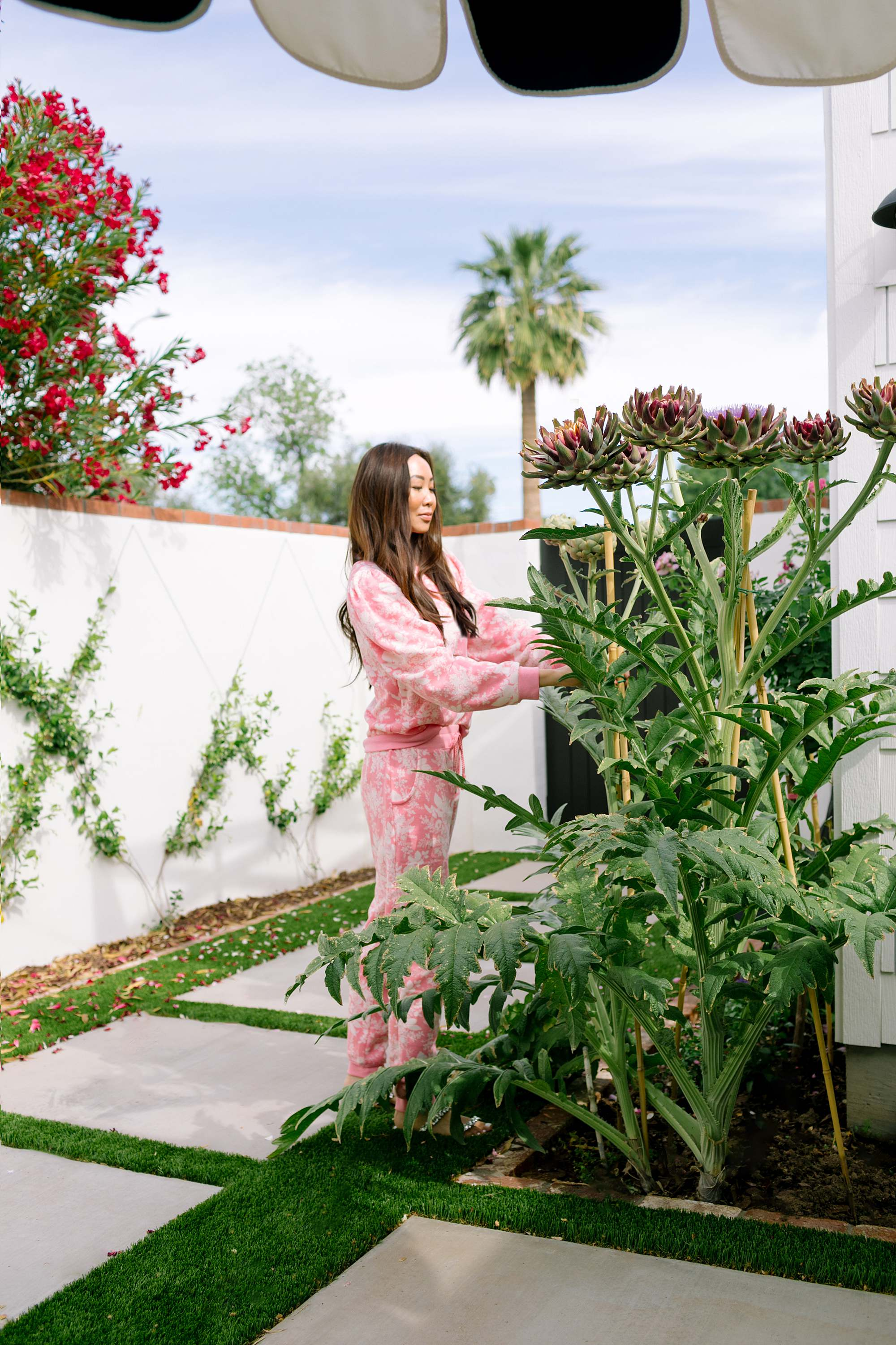 woman in pink floral loungewear standing next to large blooming artichoke plant - Diana Elizabeth blog based in Phoenix a home and garden lifestyle blog