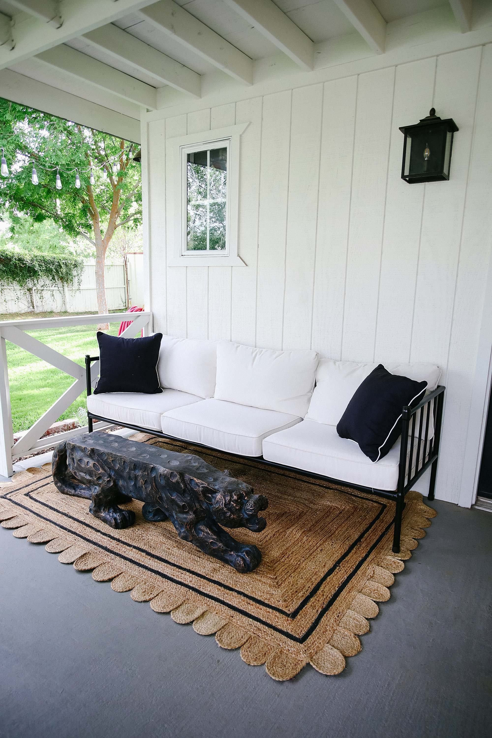 leopard bench turned coffee table, scalloped jute rug Grandmillennial style porch inspiration contemporary English garden white and black romantic feminine backyard porch vibe