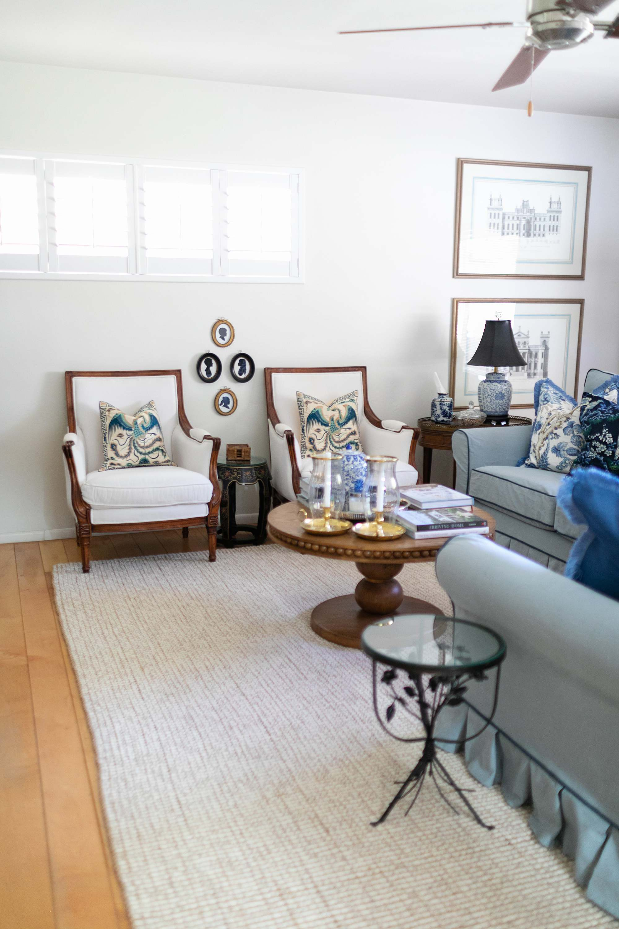 white antique wood chairs decorating with silhouette frames on the wall blue and white living room