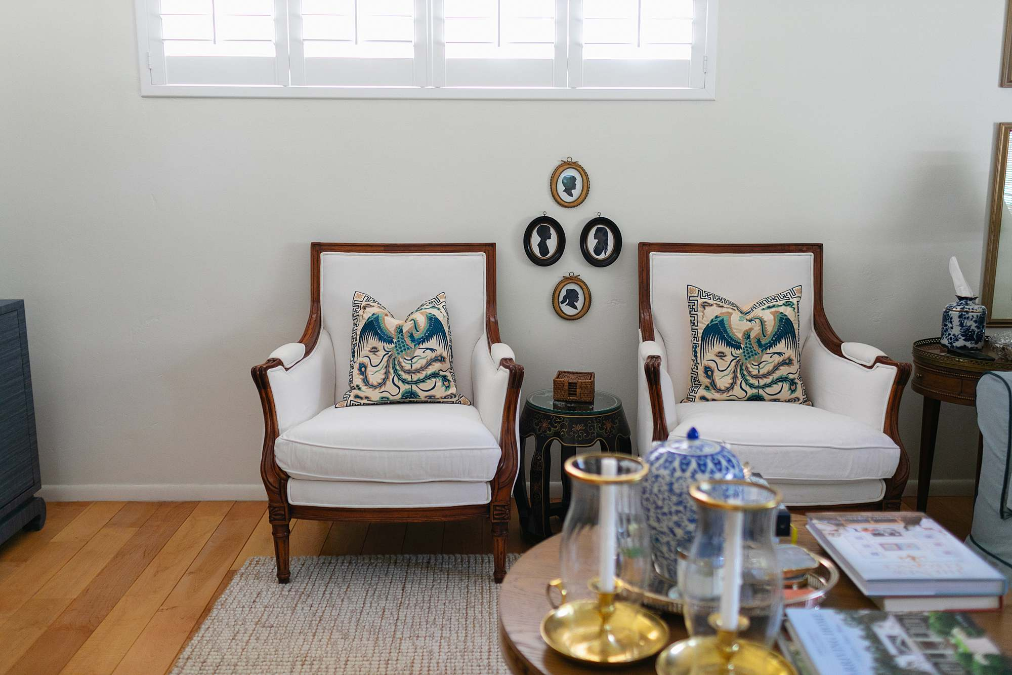 white antique wood chairs with silhouette collection hung between. blue and white living room theme brick home all American grandmillennial decoration
