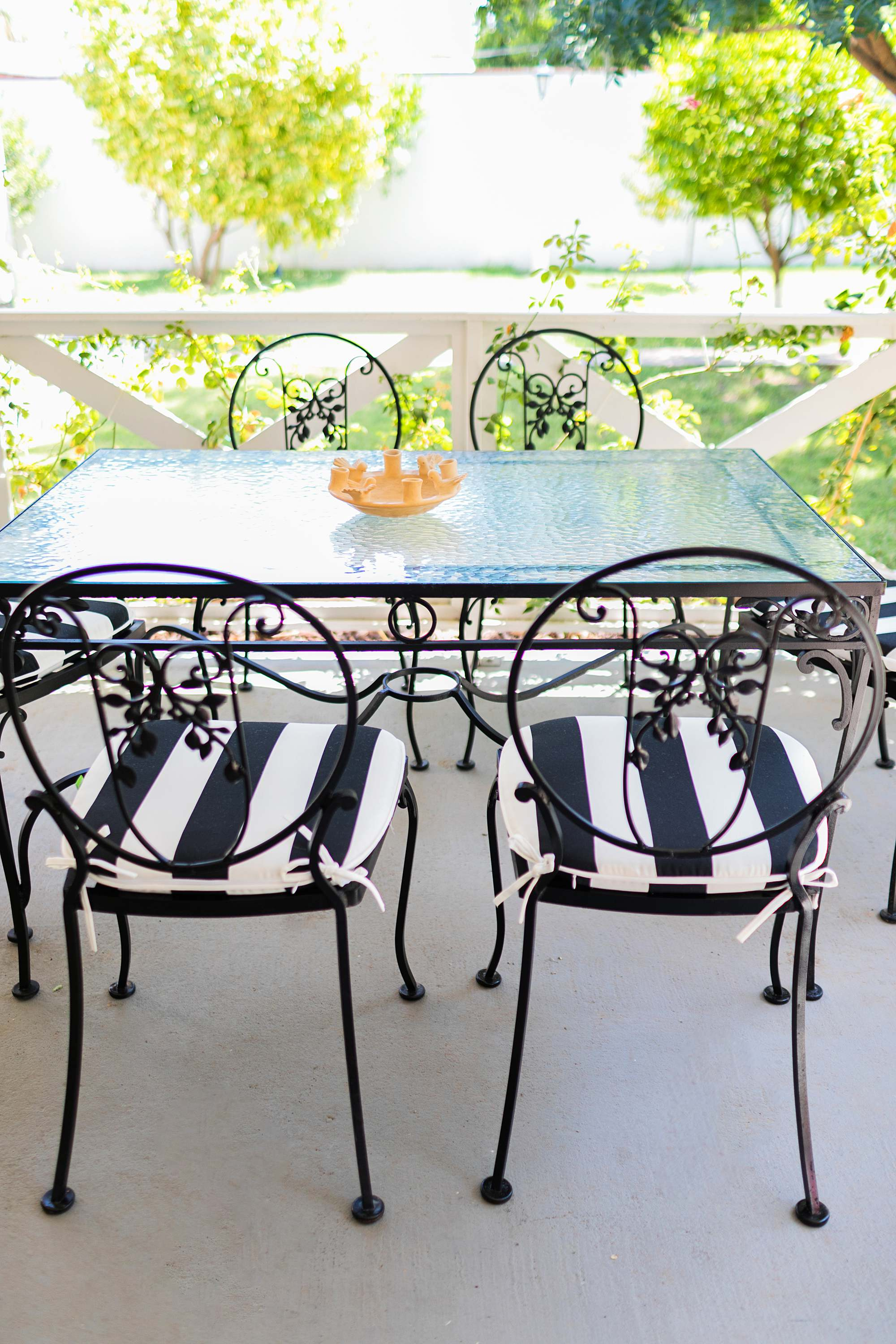 black scroll work on the midcentury modern chairs found at an estate sale with black and white stripe outdoor chair cushions from Amazon