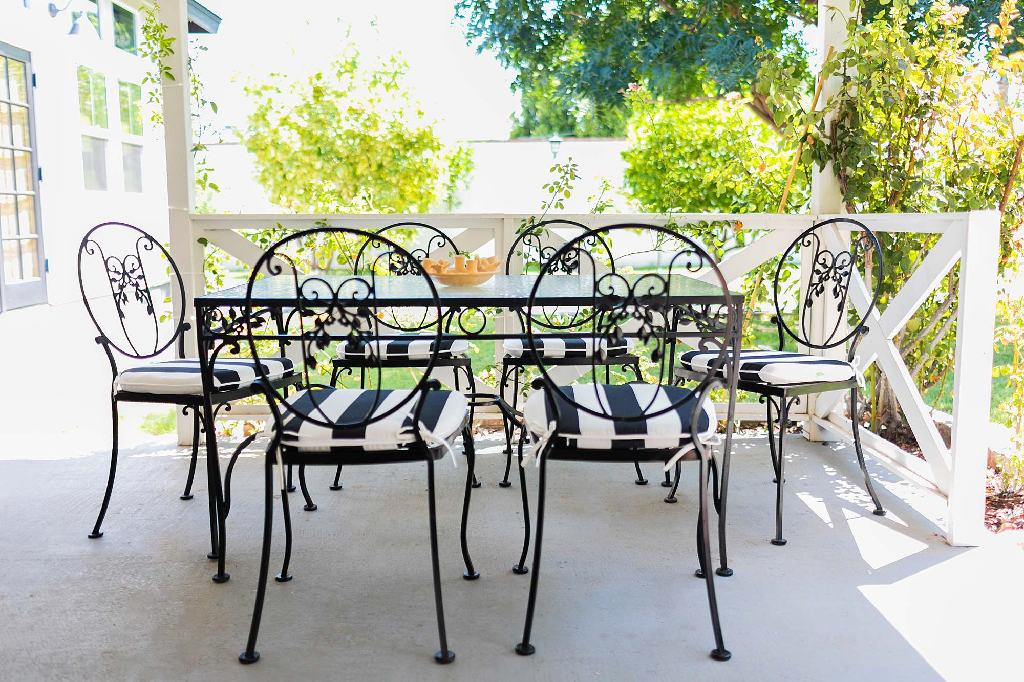 backyard small patio space black and white cushions midcentury modern table and chairs dining set