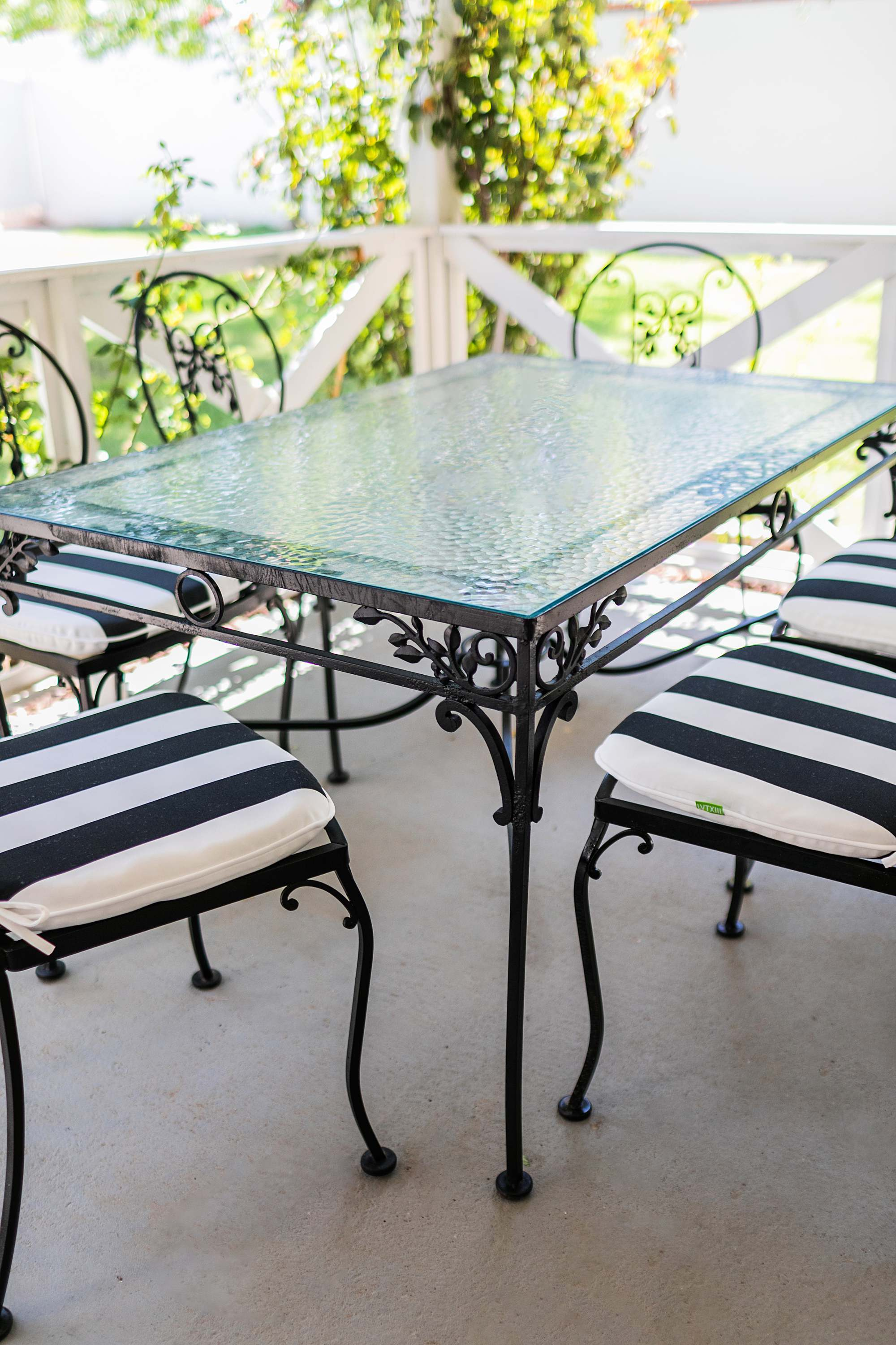 iron mid century modern grand millennial style outdoor table patio set with fresh black and white cushions from amazon - glass top phoenix lifestyle blogger Diana Elizabeth